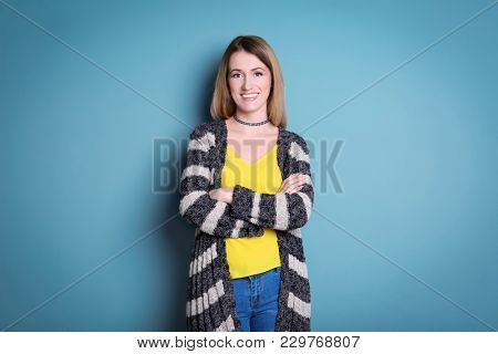 Young woman in striped cardigan on color background