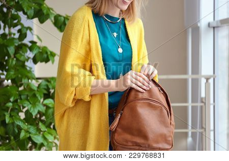 Young woman in yellow cardigan with leather backpack indoors