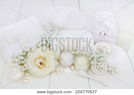 Bridal spa and beauty treatment products with rose and gypsophila flowers, ex foliating salt, moisturising cream, body lotion, sponges, wash cloths, shells and decorative pearls on white wood.