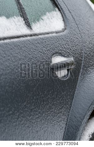 Dark Grey Car Door Covered In Black Ice On A Sub Zero Winter Morning Caused By Freezing Rain. Potent