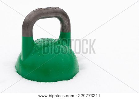 Green Weight Training Kettlebell Covered With Water Droplets Outside In The Snow. Potential Copy Spa