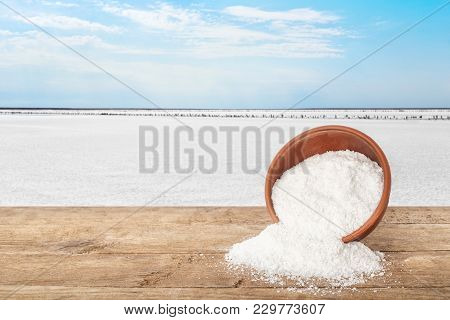 Salt In Bowl. Crystals Of Salt Scattered Out Of Clay Bowl On Table With Salty Lake In The Background