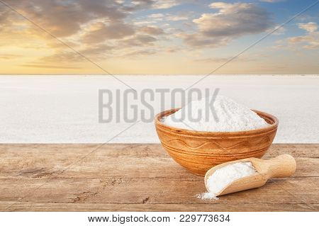 Salt In Bowl. Crystals Of Salt In Clay Bowl On Table With Salty Lake In The Background. Sea Salt Pro