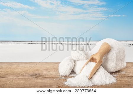 Salt And Scoop On Table. Lumps Of Salt With Salty Lake In The Background. Salt Produced On Farm