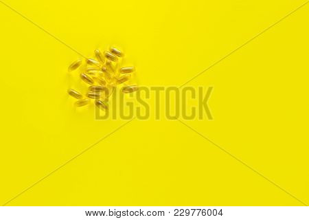 Capsules With Fish Oil Omega Three On A Yellow Background With Empty Space. Flat Lay Background For
