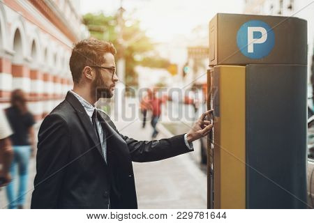 Young Handsome Businessman In Glasses And The Black Business Suit Is Paying His Parking Time Using T