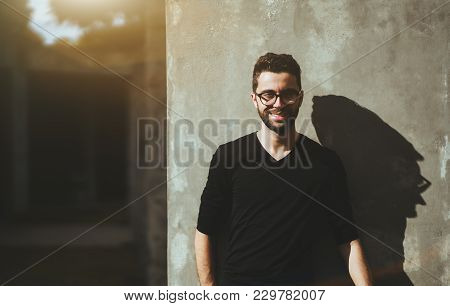 Portrait Of The Young Smiling Bearded Man With The Neat Haircut And In Glasses, Standing Near The Co