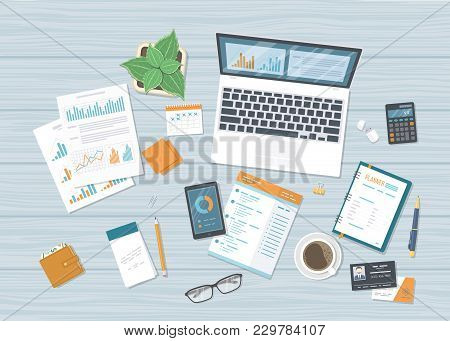 Business Workplace With Forms Charts, Graphs, Laptop With Information On The Screen, Notebook, Phone