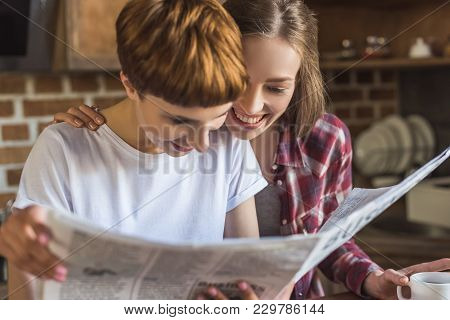 Close-up Portrait Of Young Lesbian Couple Reading Newspaper Together On Kitchen