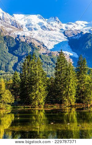 City - Park is illuminated by the sunset. The lake reflected the evergreen spruce and snow-capped Alps. The mountain resort of Chamonix, Haute-Savoie. Concept of active and ecological tourism