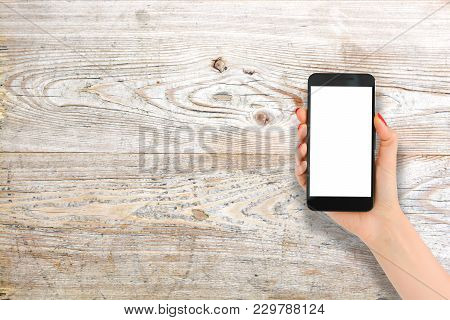 Wooden Background With Woman Hand Holding Smartphone With Blank Screen