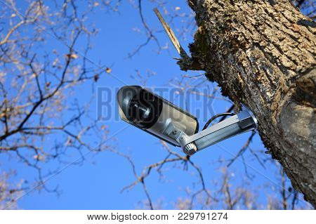 Zoom On A Video Surveillance Camera With Blue Sky Background