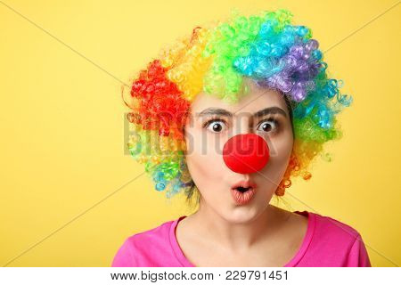 Young woman in funny disguise on color background. April fool's day celebration