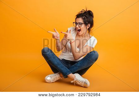 Photo of joyous girl 20s wearing eyeglasses and sneakers sitting in lotus pose on floor and pointing fingers aside excitedly over yellow background