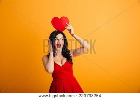 Image of fascinating woman 20s in red dress smiling and holding paper valentine heart above head isolated over yellow background
