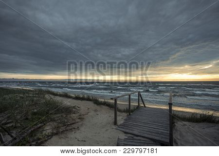 Dark Sunset On The Sea With Waves From Sand Beach On The Curonian Spit At The Summer