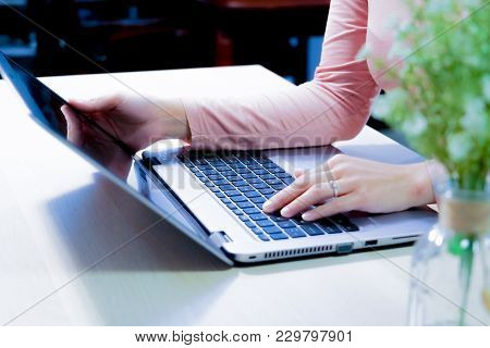 Soft Focus Of Woman Using Laptop, Searching, Checking, Browsing Information On The Wooden Table