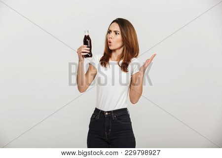 Photo of shocked young woman standing isolated over grey wall background holding bottle with soda. Looking aside.
