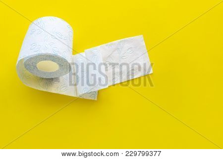 Roll Of White Toilet Paper On A Yellow Background With Empty Space.