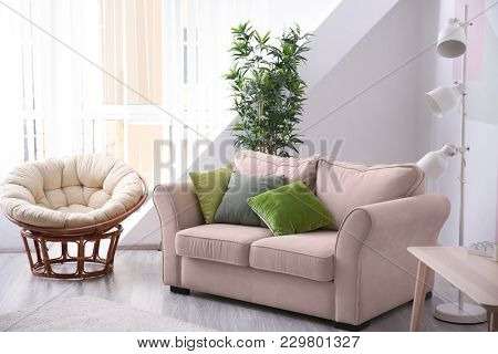 Stylish living room interior with comfortable sofa and lounge chair
