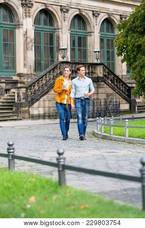 Tourist couple in Dresden having walk at Zwinger with coffee