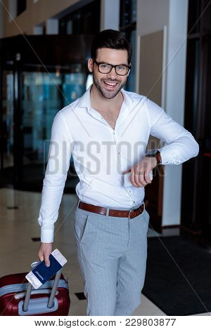 Handsome Smiling Man With Wristwatch And Wheeled Bag Looking At Camera