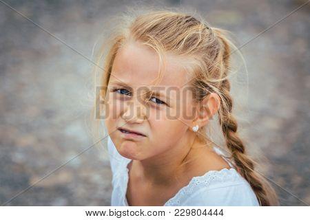 Grumpy little girl looking into camera
