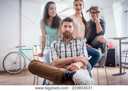 Portrait of four co-workers smiling and looking at camera, while wearing cool casual clothes during work in the shared office space of a modern hub for freelancers and young entrepreneurs