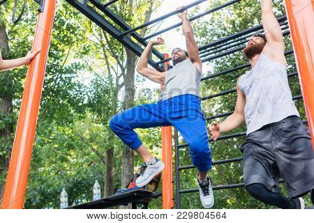Low-angle view of two strong and competitive men exercising on monkey bars for the upper-body in a modern calisthenics park