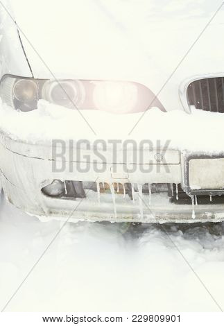 Winter, Frost. A Silver Car With The Light Turned On In The Headlight. The Car Under The Snow Was St