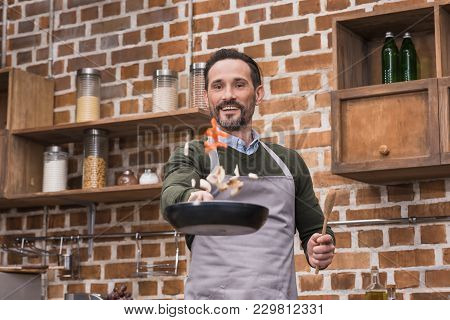 Handsome Man Tossing Up Vegetables On Frying Pan