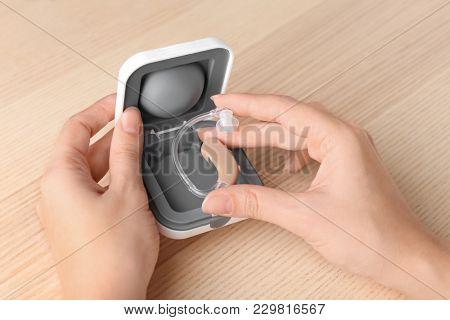 Woman holding hearing aid, closeup