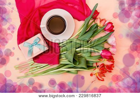 White Cup Of Coffee With Tulips And Gift Box. Top View.