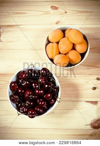 Fresh Apricots And Cherries Berries On Wooden Background. Top View.