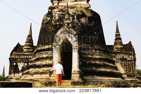 Tourist Man With Camera Is Walking In To An Ancient Ruined Stupa In Ayutthaya Historical Park, Thail