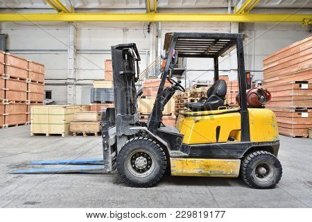 The Forklift Is Old And Scratched In A Large And Light Warehouse. Yellow Color