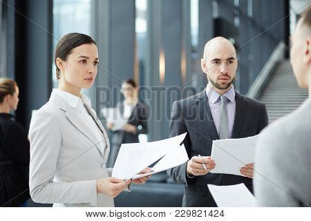 Two serious financiers with financial documents looking at expert during discussion of latest news