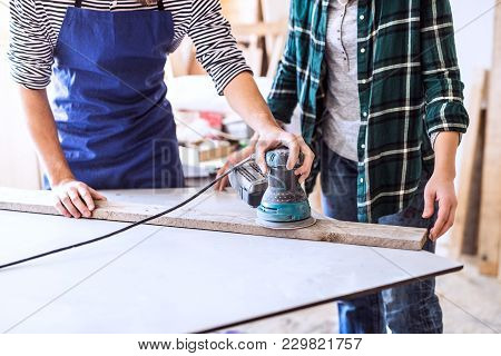 Small Business Of A Young Couple. Unrecognizable Man And Woman Worker With A Sander In The Carpenter