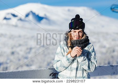 Concept Snowboarding. Young Woman Holds Snowboard And Looks Track For Descent, Chooses Path.