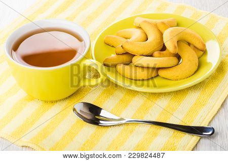 Shortbread In Form Crescent In Saucer, Cup Of Tea, Spoon On Yellow Napkin On Wooden Table