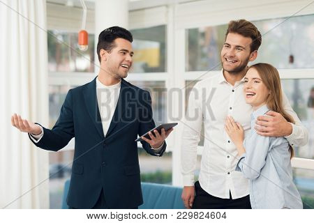 Young Couple In A Meeting With A Realtor. A Guy And A Girl Make A Contract With A Realtor About Buyi