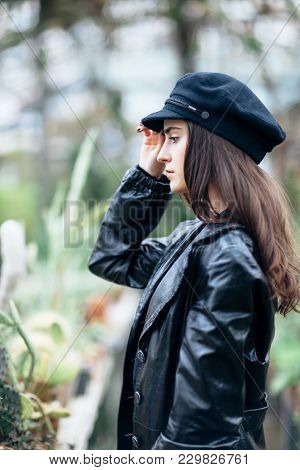 Profile Portrait Of Young Fashion Woman In Leather Jacket And Cap