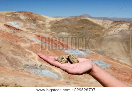 The Cerro Rico Hillside And Ore Silver On The Hand In The Background Of The Mining Conglomerate