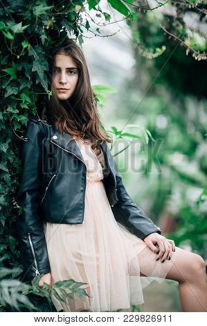 Fashion Portrait Of Young Stylish Woman In Pink Dress And Leather Jacket Posing