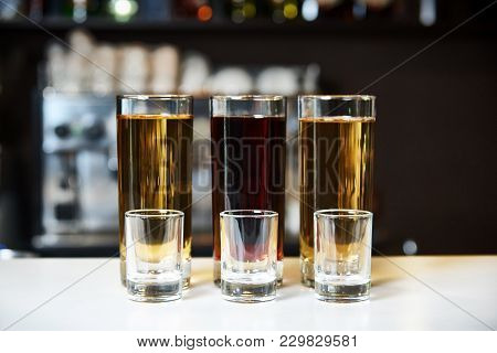 Alcohol Shots And Empty Stemware On The Background Of A Blurry Bar.