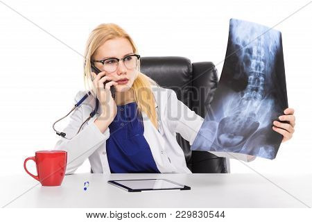 Hesitating Female Doctor Physician In White Coat And Glasses Sit At Table Studies X-ray Consults Dig