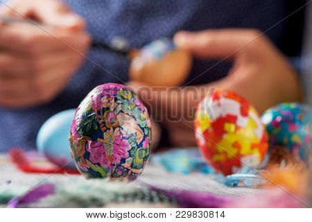 closeup of a young cacausian man decorating some homemade easter eggs by gluing some pieces of different papers, on a gray rustic wooden table sprinkled with feathers of different colors