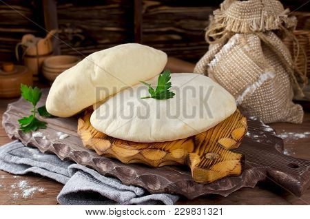 Homemade Whole Pita - Baked Israeli Flat Bread. Pita Bread On Wooden Cutting Board
