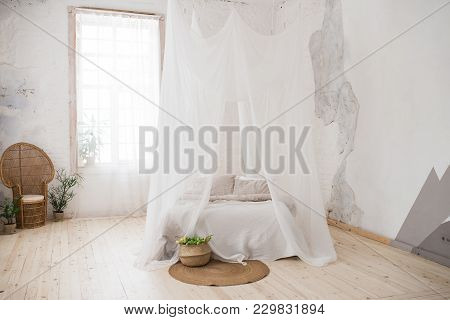 Double Bed With Gray Bed Linen And Canopy. Bedroom. A Wicker Chair Made Of Wood In The Corner Of The