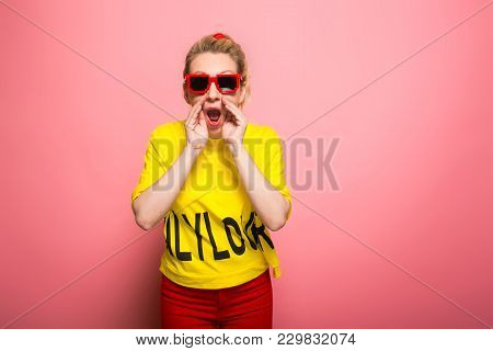 Attractive Woman In Yellow T-shirt, Red Jeans And Sunglasses Holding Her Hands Near Mouth Calling So